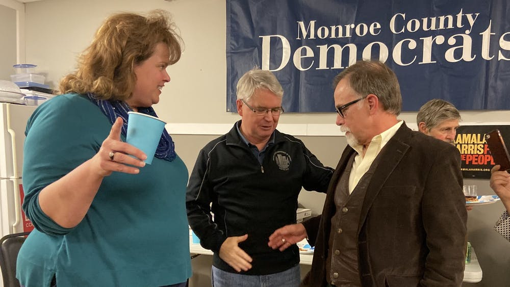 Mayor John Hamilton, center, and Ron Smith shake hands while talking with Sue Sgambelluri on Tuesday night at the election watch party for the Monroe County Democrats. Smith won the election for Bloomington City Council District 3, and Sgambelluri won the District 2 race.