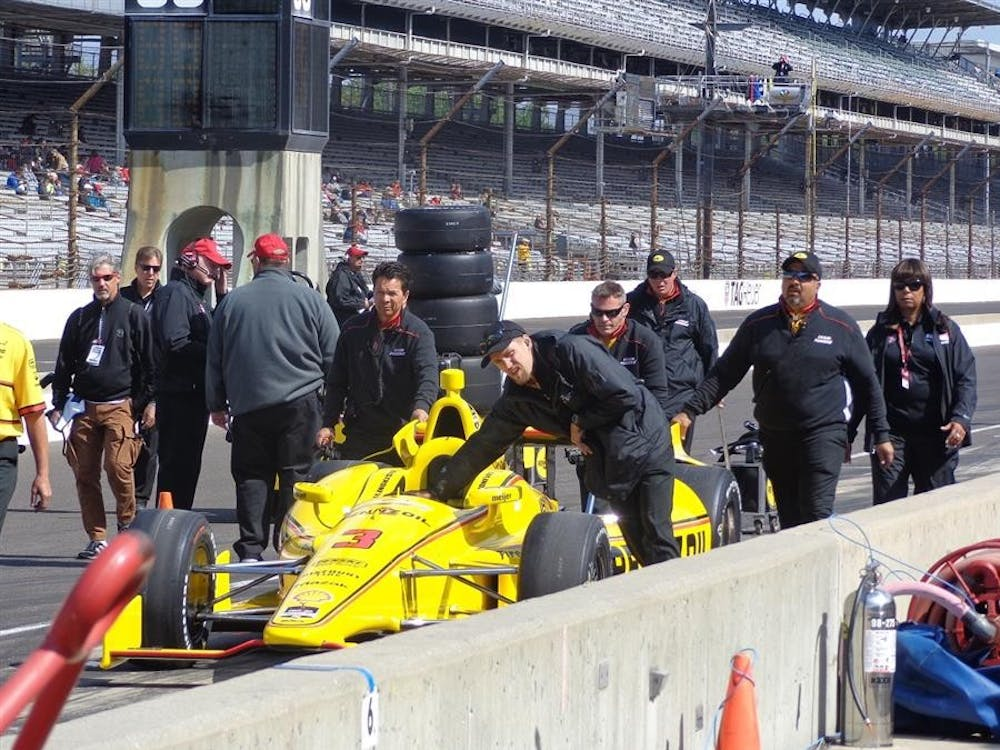 Three-time winner Helio Castroneves' car is pushed down pit road during qualifications by crew members May 17 at Indianapolis Motor Speedway.