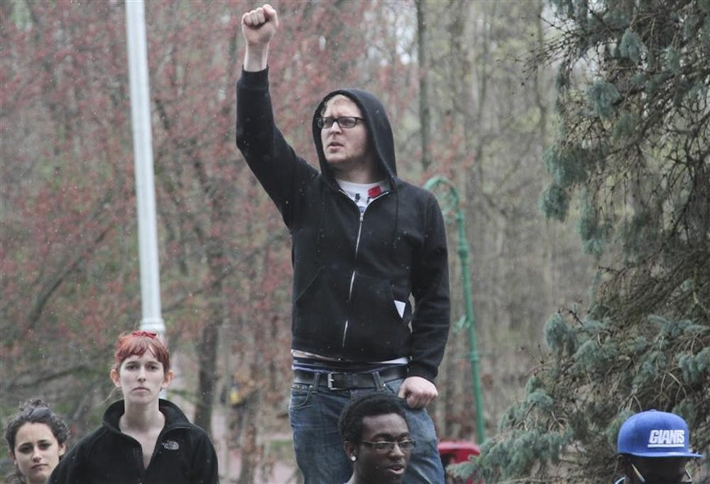 An IU on Strike protester pumps his fist in the air outside of Franklin Hall to show solidarity with the movement. Protesters marched throughout campus on their way to the Board of Trustees meeting at Franklin Hall.