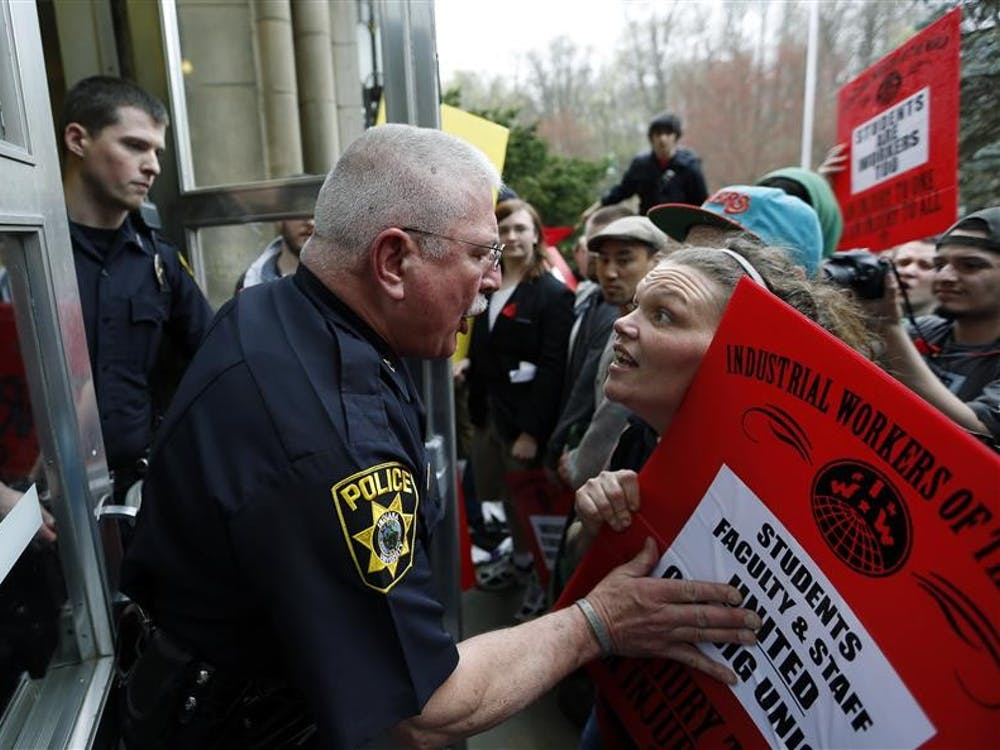 Capt. Thomas Lee of the IU Police Department argues with a IU on Strike protester attempting to enter Franklin Hall during a Board of Trustees meeting.