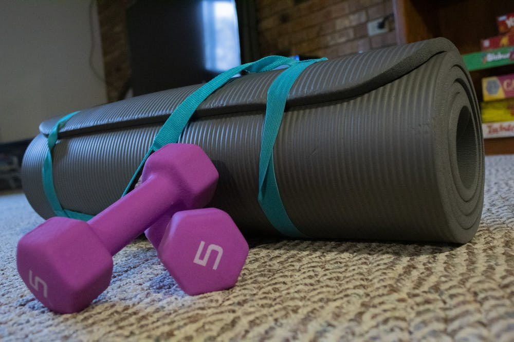 <p>A workout mat and set of weights sit on the ground. </p>