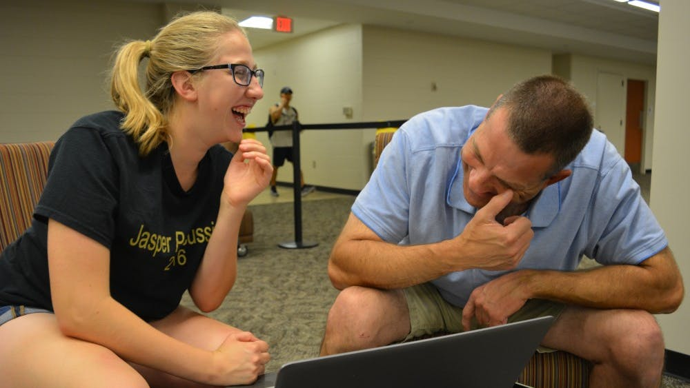 Freshman Elizabeth Ketzner and her father, Brian Ketzner, laugh while listening to a recording of Elizabeth's grandfather in Wells Library on Oct. 3. Because her grandfather died when Elizabeth was a baby, she had no memory of what he sounded like.