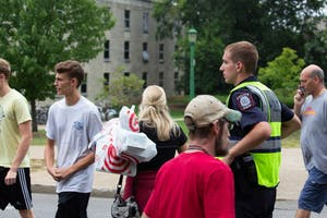 An IU police officer assists people at a crosswalk during move-in week Aug. 15 between Wright and Teter quads.