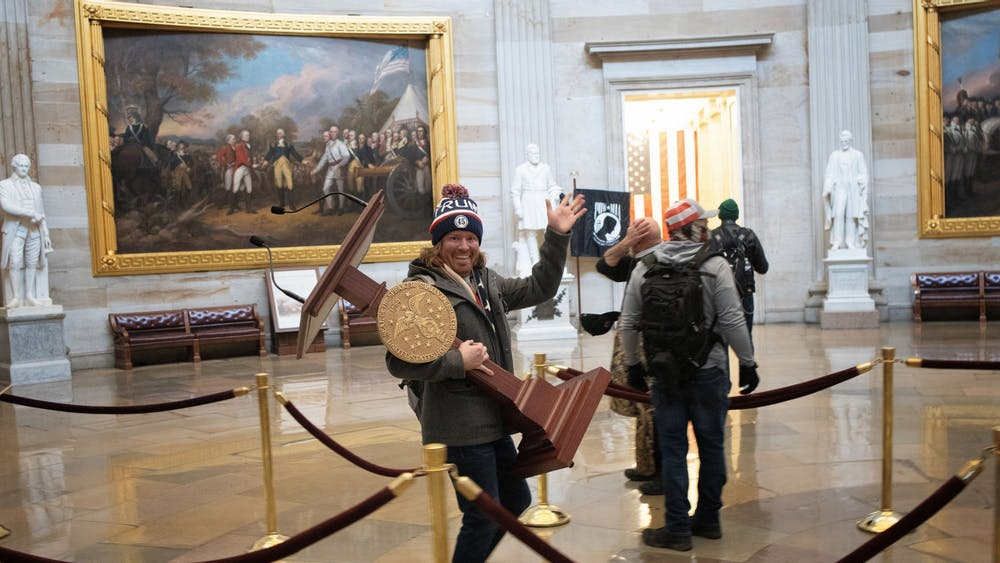A rioter takes the lectern of U.S. Speaker of the House Nancy Pelosi through the U.S. Capitol Building after a pro-Trump mob swarmed the building on Jan. 6 in Washington, D.C. Items were stolen and damaged by rioters, including furniture, windows and artifacts.