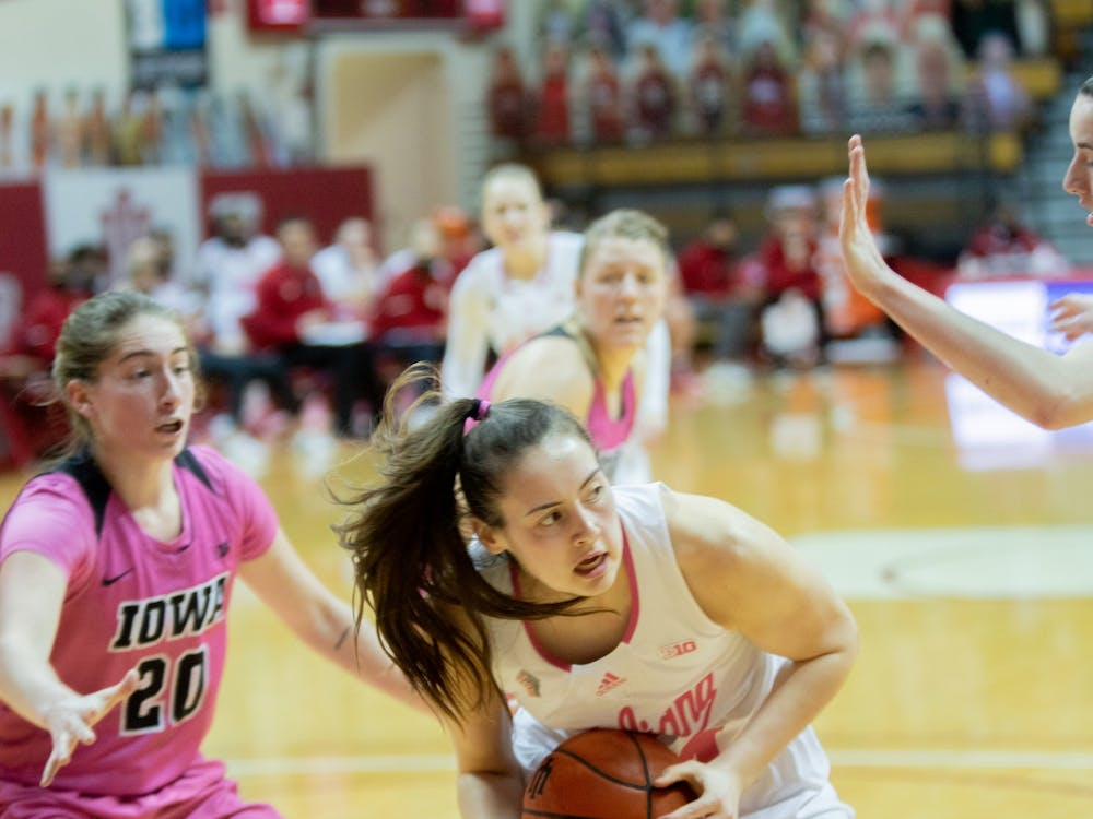 Sophomore forward Mackenzie Holmes secures the ball against the Iowa defense Wednesday at Simon Skjodt Assembly Hall. The Hoosiers were down 38-43 to the Hawkeyes at halftime.