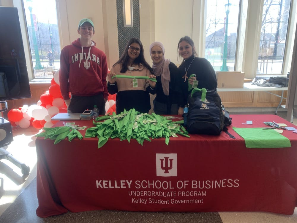 Kelley Student government delegates Paul Obrecht and Kacey Cook (left and right ends) pose with Kelley Student Government Vice President of membership Rashi Sarraf (middle-left) and Director of Ethics and Social responsibility Zahraa Ouyuon (middle-right), for a photo March 5 while handing out green bandanas in Hodge Hall. Nine different organizations handed out green bandanas for students to tie on their backpacks to show support for those struggling with mental health.