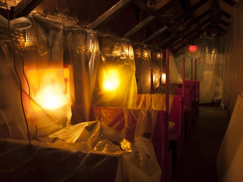 The first floor dining room of Nick's English Hut sits under construction tarps and work lights Monday afternoon.
