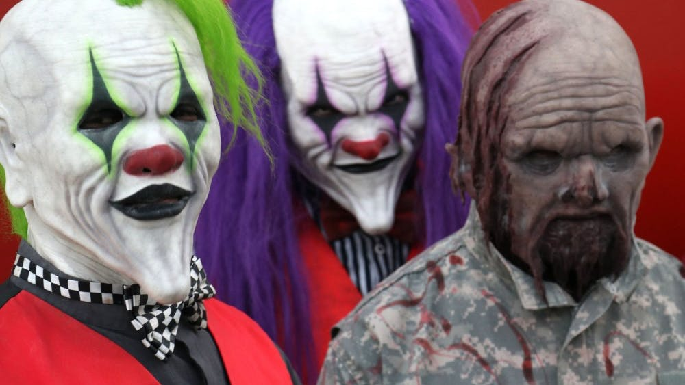 Actors with makeup and costumes stand Oct. 23 at Indy Scream Park in Anderson, Indiana. The park features five different types of haunted houses, plus a separate midway area.