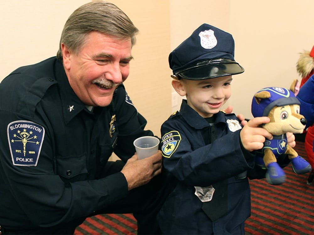 """Graycin Ryan, 4, shows off his stuffed canine to Bloomington Police Department Chief Mike Diekhoff at the """"Coffee with a Cop"""" event Monday at Hyatt Place. BPD officers and personnell met with Bloomington residents at the Hyatt Place to answer questions and chat in an informal setting."""