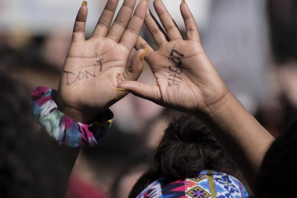 """<p>A student whose hands read """"don&#x27;t shoot"""" holds her hands in the air during a 2018 high school walkout.</p>"""