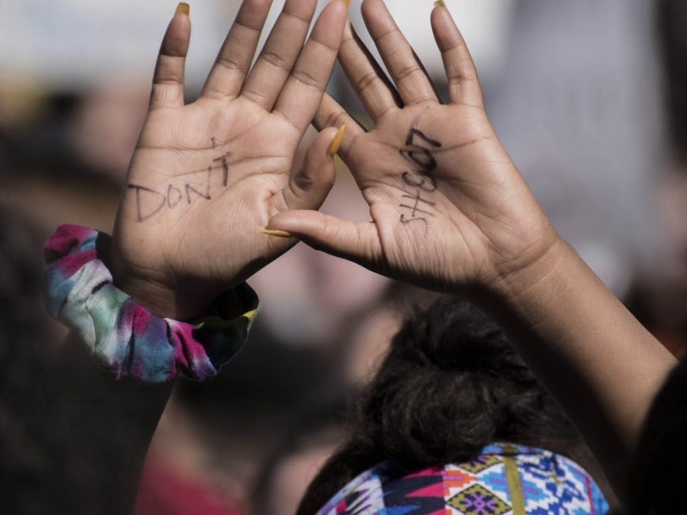 "A student whose hands read ""don't shoot"" holds her hands in the air during a 2018 high school walkout."