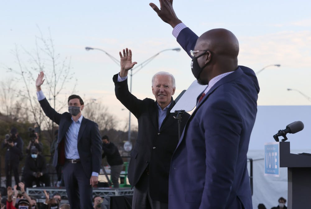 <p>President-elect Joe Biden, along with Senator-elects Jon Ossoff and Rev. Raphael Warnock, greet supporters on Jan. 4, 2021 during a campaign rally in the parking lot of Centerparc Stadium in Atlanta.</p>