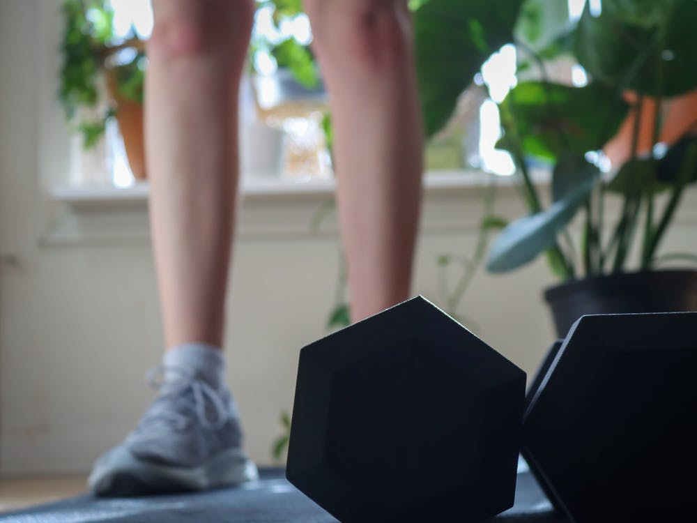 A student uses dumbbells to do a strength workout Feb. 6 in her apartment.