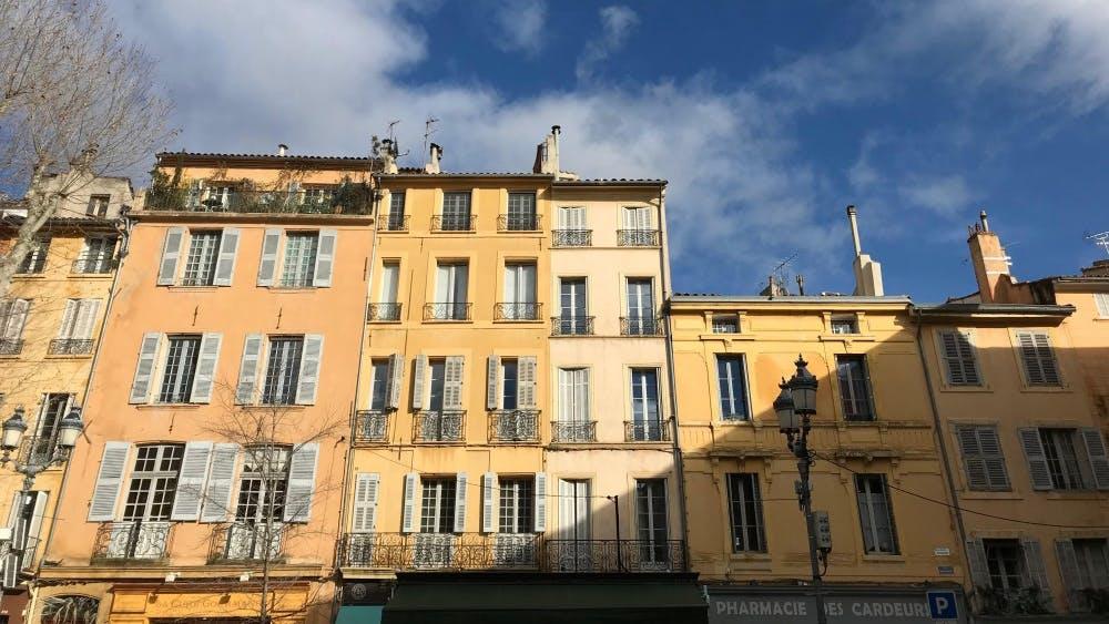 Midafternoon sunlight strikes the building facades in Place de l'Hôtel de Ville, a plaza in Aix-en-Provence, France.