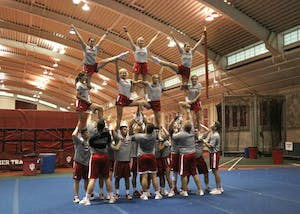 IU's Cream co-ed cheerleading squad works on a pyramid structure at practice. Some of the females on the team are off the ground and supporting others in the air at the same time.
