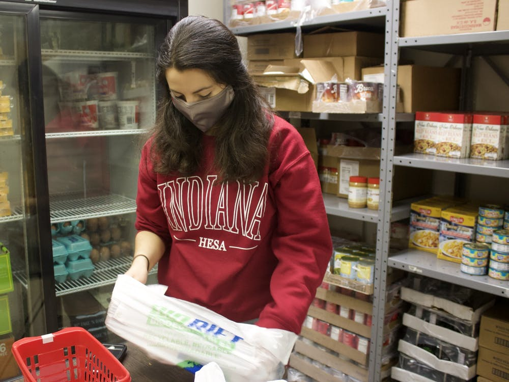 First year master's student Daniella Feijoo fills bags for clients to take Monday at Crimson Cupboard. Feijooo is in her first year as a graduate assistant at Crimson Cupboard.