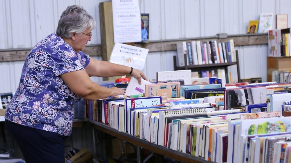 Rullen Fessenbecker searches for books at the Bloomington Community Book Fair, hosted by Hoosier Hills Food Bank. Fessenbecker, who lives in Nashville, Indiana, has visited the book fair more than 10 times.