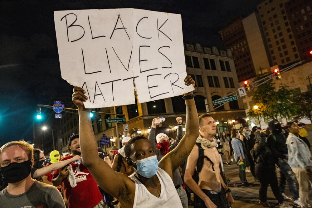 """<p>A protester holds a sign in the air May 30 in downtown Indianapolis. """"Black lives matter,"""" the sign read.</p>"""