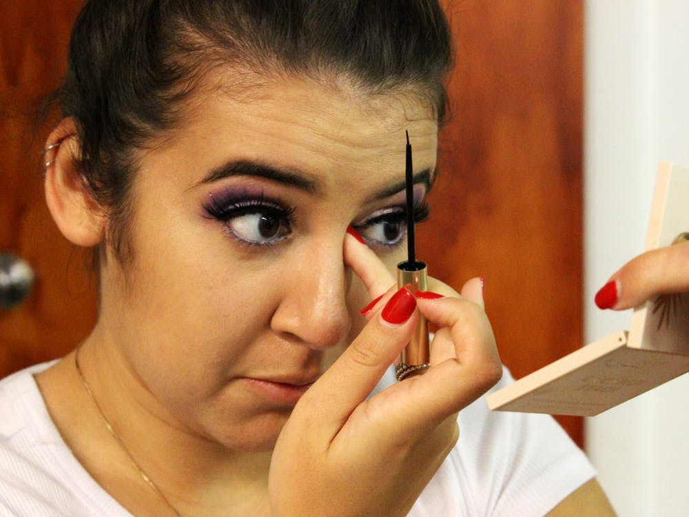 IU graduate Vanesa Quiroga applies liquid eyeliner over her fake eyelashes Sept. 26 backstage of the 15th annual Fiesta de Otoño. Her purple eyeshadow matched her quinceañera gown.