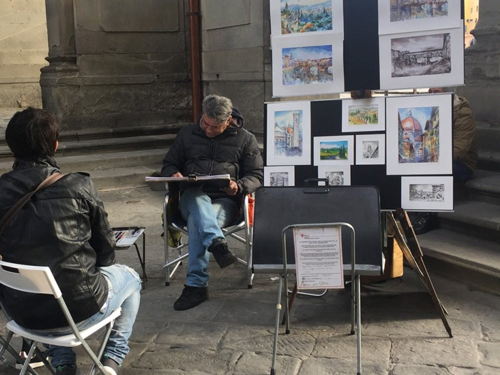 An artists practices his craft on the side streets of Florence, Italy. His work can be surprising to the viewers because of his skill.