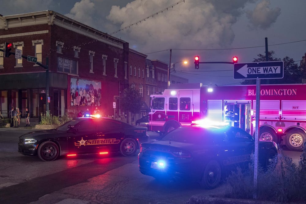 <p>Sheriff's department cars and a Bloomington Fire Department truck sit with their lights flashing at the intersection of Sixth and Walnut Streets after multiple protesters were hit by a car just after the conclusion of the protest July 6 in downtown Bloomington. The protest was in response to a racist attack on Monroe County human rights commissioner Vauhxx Booker on July 4.</p>