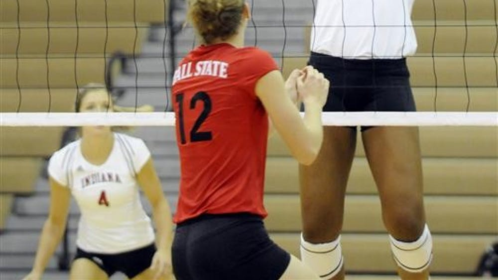 IU freshman Lexie Woodson, No. 14, sets the ball as Ball State's Jennifer Boyd, No. 12, watches from across the net during the TIS Bookstore Invitational on Friday, Sept. 19 at University Gym. IU swept Ball State 3-0.