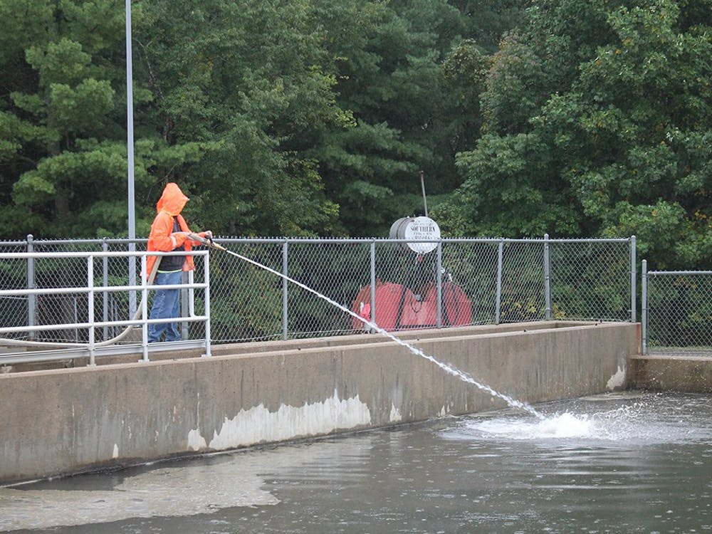 A worker sprays water into the basins to break up sediment that collects at the top at the Monroe Water Treatment Plant. An equipment malfunction occurred at the Monroe Water Treatment Plant that may cause some Bloomington residents to have a harmless pink tint to their water, according to a Saturday release.