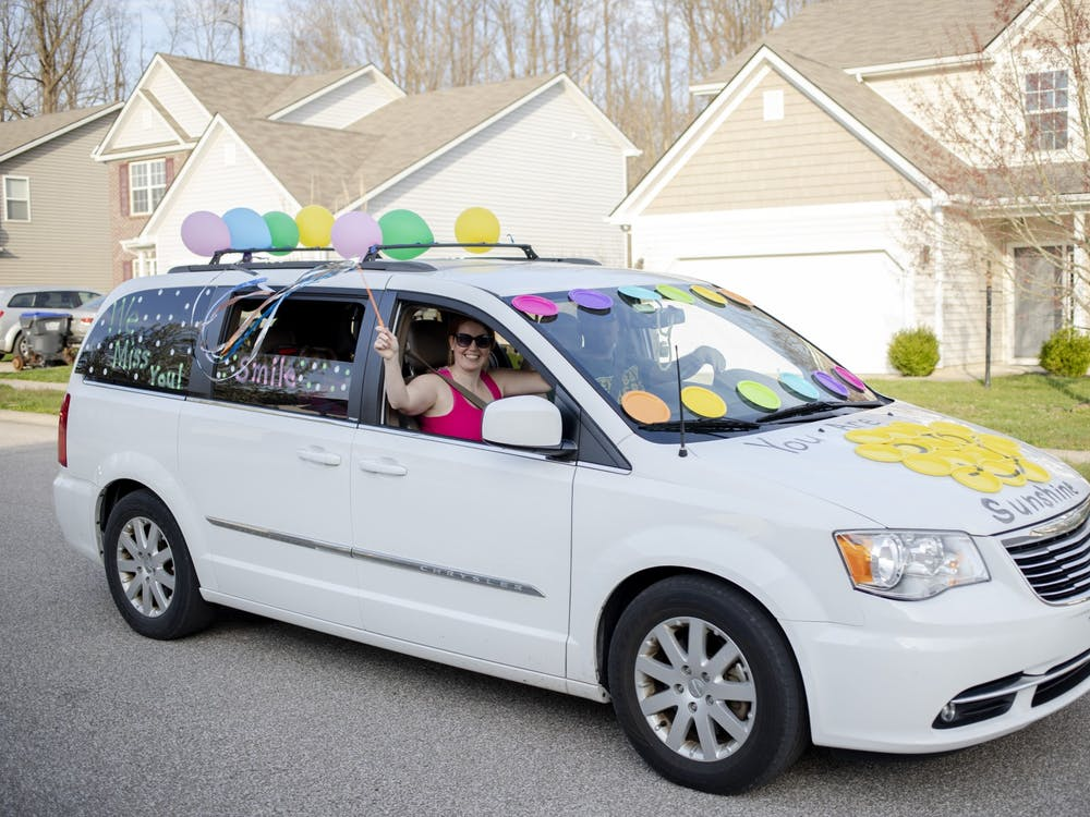 A Summit Elementary School teacher waves a ribbon wand out her window April 3 on South Glasgow Circle. The van led a line of cars throughout neighborhoods in the school district.