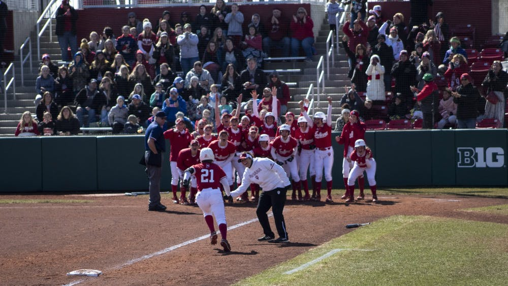 Then-freshman Juvia Davis is greeted March 17, 2019, by her teammates at home plate after hitting a grand slam for the Hoosiers. IU softball will travel nearly 10,000 miles in its first 26 games this season.