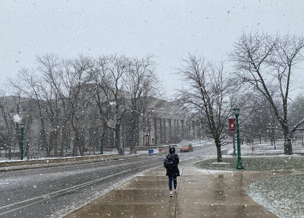 An IU student walks through the snow Feb. 9 on Jordan Avenue. Bloomington is expected to receive up to an inch of snow late Tuesday, according to the National Weather Service.