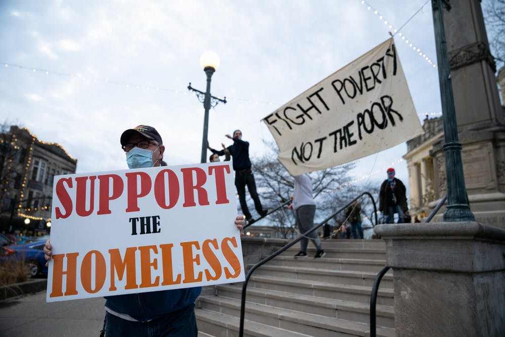 <p>A protester holds a sign as others raise a banner Dec. 11 at the Monroe County Courthouse. The protest was in response to the Bloomington Police Department and other personnel  forced the homeless camp in Seminary Square Park to leave. </p><p><br/></p>