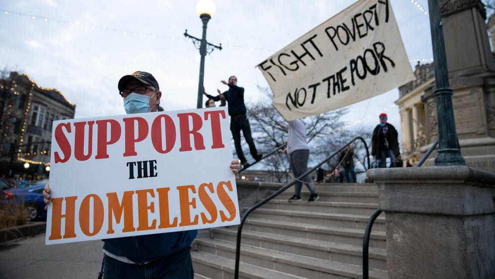 A protester holds a sign as others raise a banner Dec. 11 at the Monroe County Courthouse. The protest was in response to the Bloomington Police Department and other personnel  forced the homeless camp in Seminary Square Park to leave.