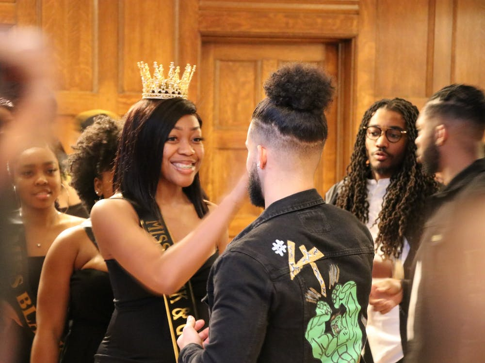 Senior Marsha Jean-Baptiste gives a high-five to senior Brendan Berry before Alpha Phi Alpha's new member presentation Sunday in Alumni Hall. New members were introduced to friends and family at the ceremony.