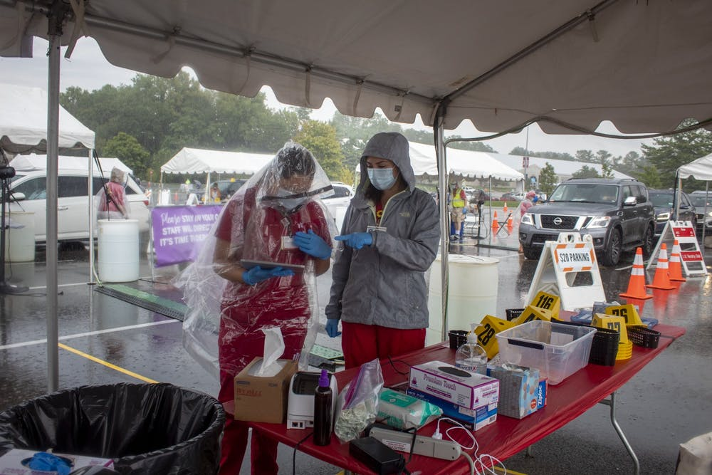 <p>Nursing students Jessica Gutierrez and Ericka Alvarez work at a COVID-19 testing center Aug. 18 near Memorial Stadium. Students moving into Residential Programs and Services housing go through four different checkpoints before moving into their assigned dorms.</p>