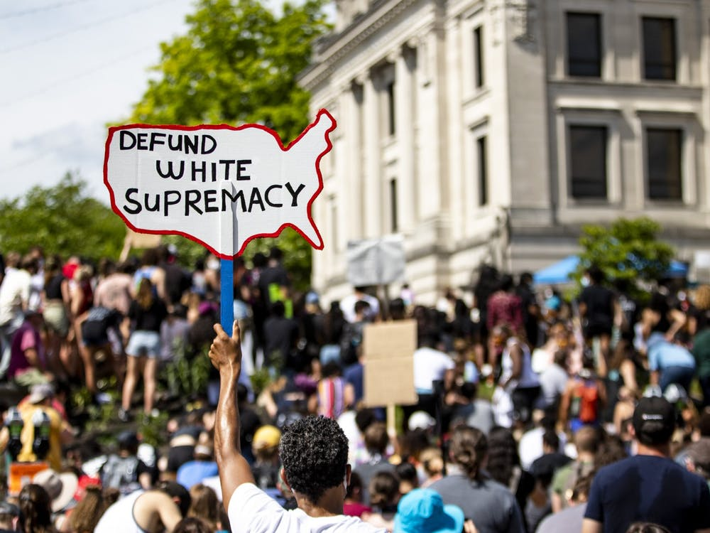 A protester holds up a sign while kneeling June 5 in front of the Monroe County Courthouse. An article from the Washington Post says that more Black people are screening positively for depression or anxiety in the wake of the killing of George Floyd.