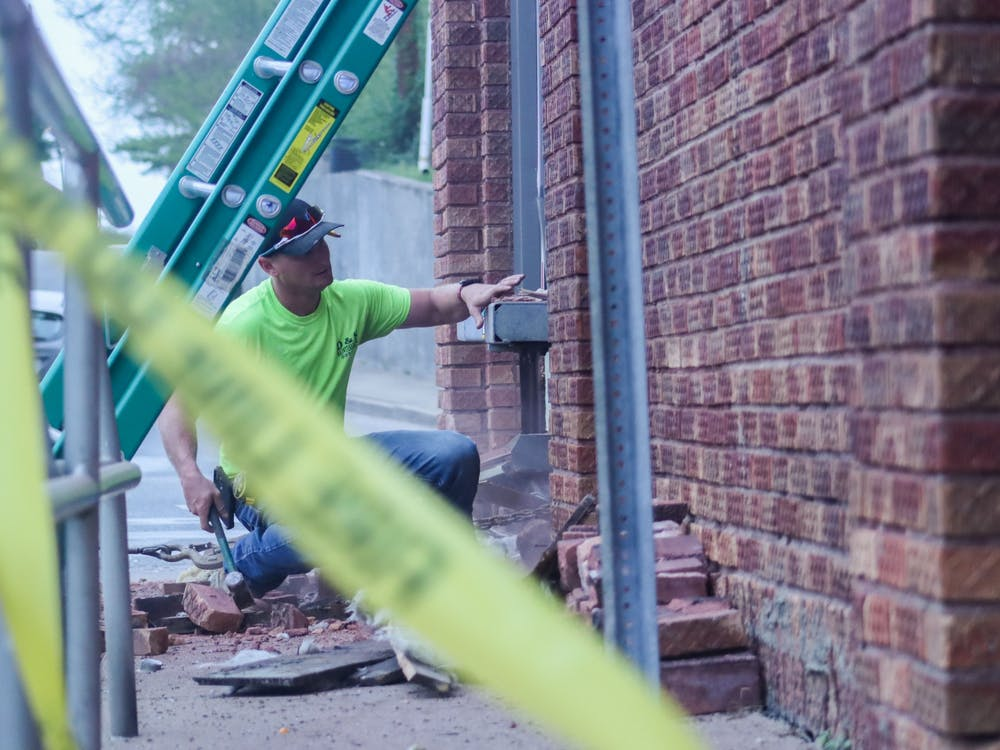 Tyler Deckard of D & S Maintenance Inc. uses a sledge hammer to break through brick at Evil by the Needle on Sunday night. Maintenance workers swept debris from the opening to board it up.