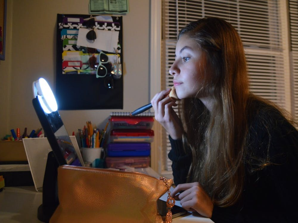 Sara Sofia Carmona applies makeup in the corner of her room. While Sara Sofia enjoys artistic pursuits like makeup, calligraphy and singing, she also excels in math at school.