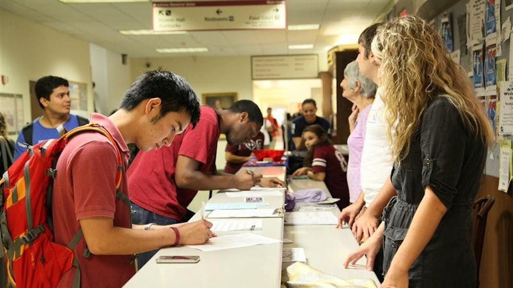 Sophomore Antony Vo fills out paperwork at the voter registration Wednesday at the Indiana Memorial Union.