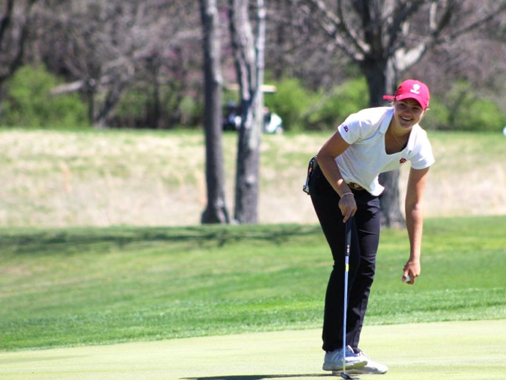 Then-freshman Emma Fisher picks her ball out of the hole after sinking a putt April 8, 2017, during the IU Invitational at the IU Golf Course. IU shot 19-over-par during the Westbrook Invitational Feb. 23-24 in Peoria, Arizona.