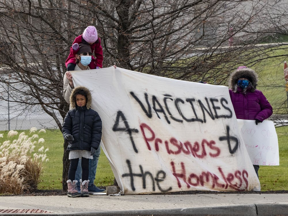 Protesters watch as the vice presidential motorcade arrives Dec. 15, 2020, outside of Catalent in Bloomington. People experiencing homelessness have a high risk of contracting COVID-19.