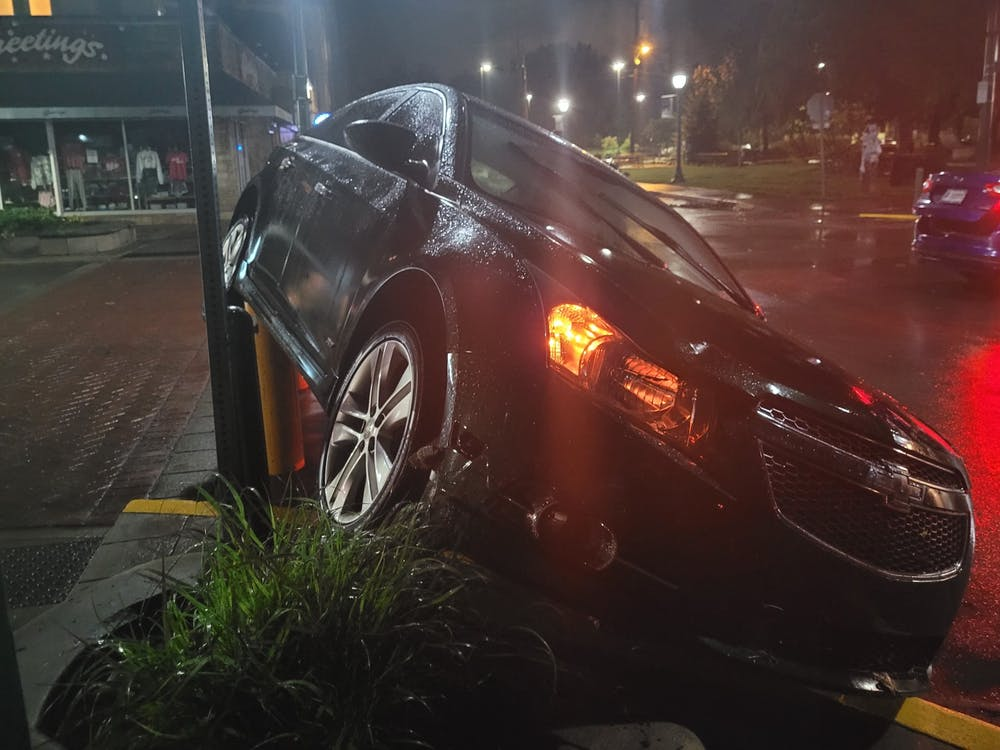 A car is pictured partially on its side on top of a curb June 18 after a flood on Kirkwood Ave.