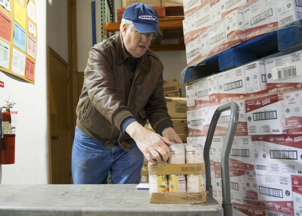 <p>First United Methodist Church volunteer Steve Ulrey unloads cans of peaches in 2017 at the Hoosier Hills Food Bank. The Hoosier Hills Food Bank has a new Fresh Fridays initiative.</p>