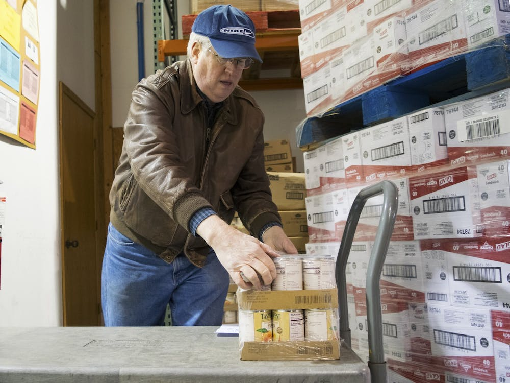 First United Methodist Church volunteer Steve Ulrey unloads cans of peaches in 2017 at the Hoosier Hills Food Bank. The Hoosier Hills Food Bank has a new Fresh Fridays initiative.