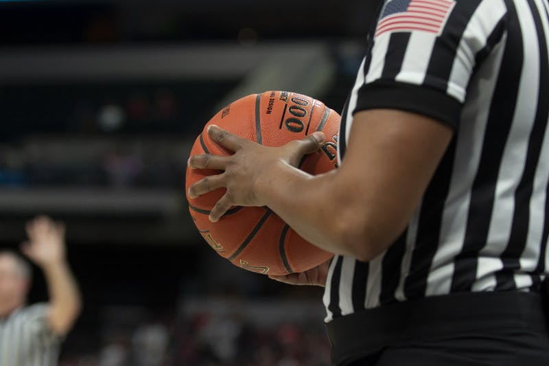 A referee holds a basketball March 6 at Bankers Life Fieldhouse in Indianapolis. IU men's basketball team has paused workouts after multiple positive coronavirus cases.