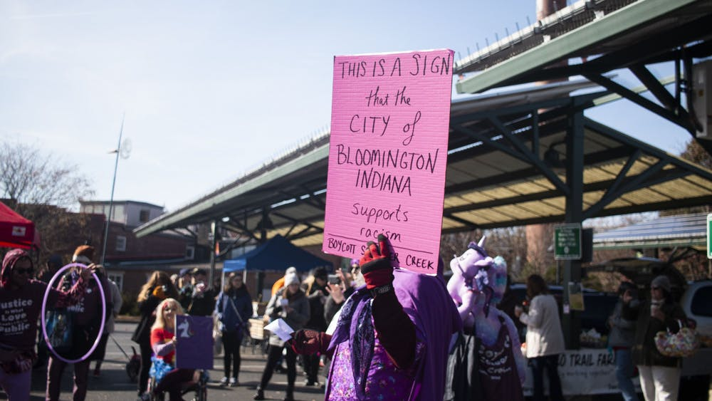 Tom Westgard carries a sign Nov. 9 through the Bloomington Community Farmers' Market in protest of Schooner Creek Farm, whose owners have been tied to a white nationalist group.  Five protesters cited at the Nov. 9 farmers market will not face charges.