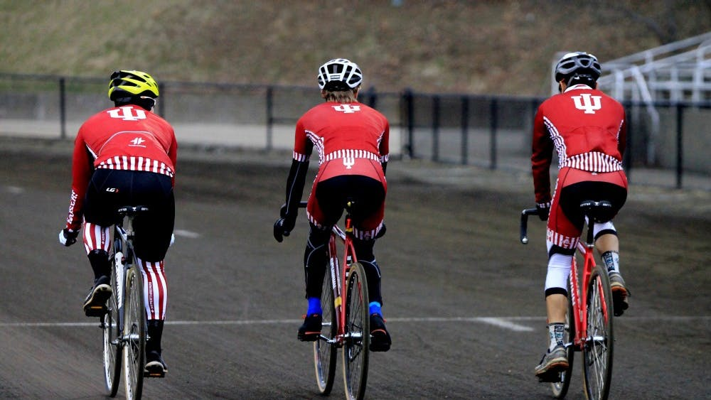 IU students Abel Duran, Michael Schmahl and Kurtis Greer ride their bikes around the track at Bill Armstrong Stadium. The IU Cycling Club has organized a home meet for March 10.