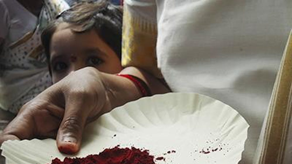 Our study abroad program director holds a plate of vermillion during Bonalu. A pinch of the powder is traditionally applied to the forehead while visiting temples.