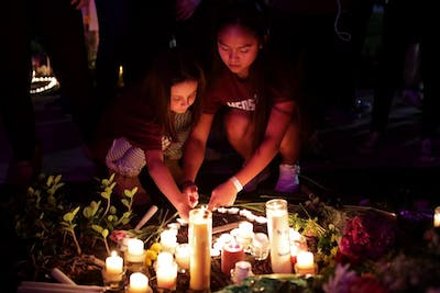 People light candles for a makeshift memorial Feb. 14 after an interfaith ceremony at Pine Trails Park in Parkland, Florida, to remember the 17 victims killed last year at Marjory Stoneman Douglas High School.
