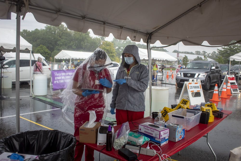 <p>Nursing students Jessica Gutierrez and Ericka Alvarez work at a COVID-19 testing center Aug. 18 near Memorial Stadium. IU will be replacing Vault Health, the company currently processing the university&#x27;s mitigation testing, with new on-campus labs.</p>