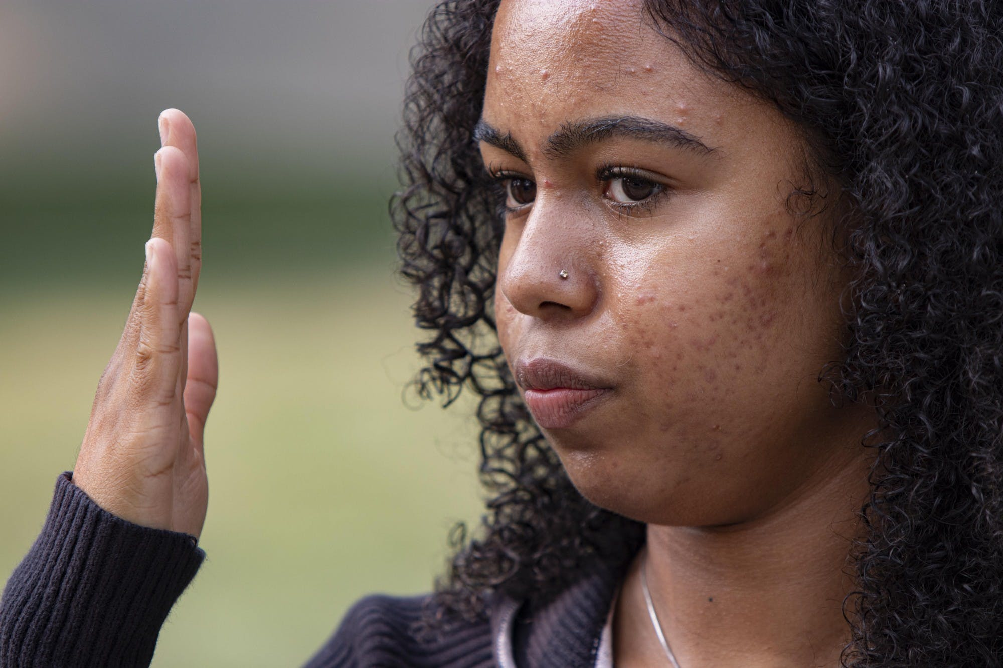 Junior Alice Aluko describes the act of bias she experienced her freshman year at IU on Sept. 15 at the corner of Third Street and Indiana Avenue. Aluko shows how close the verbal attacker was to her face with her hand.